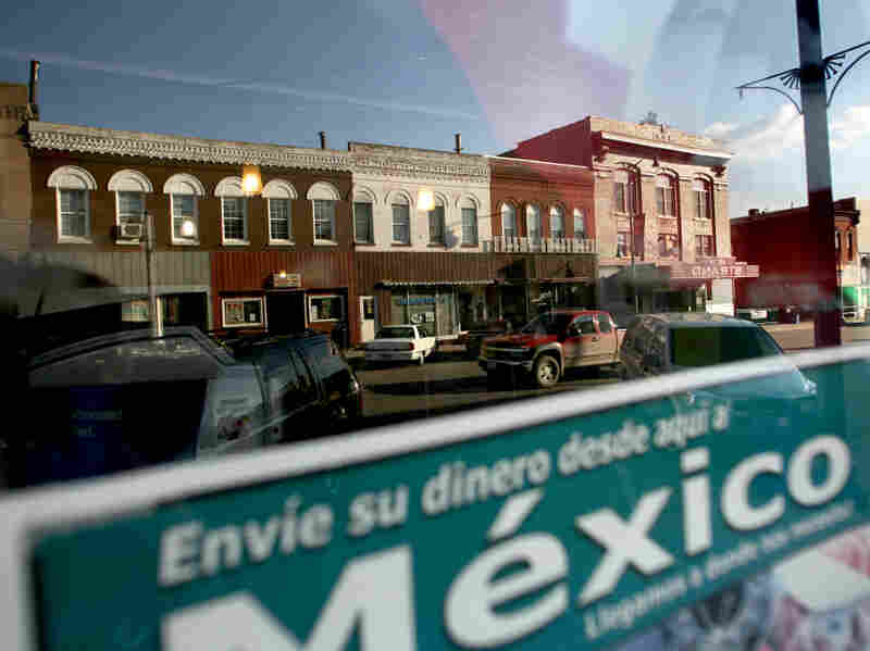 Sending money to relatives in Mexico is a popular way for families to support each other. West Liberty's East 3rd Street is reflected in this window.