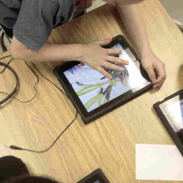 Students in a special education classroom hunch over iPads provided by the school district at Adams Elementary School in Coon Rapids, Minn.