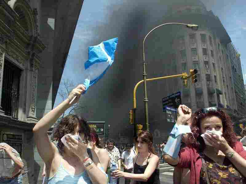 Protesters in Argentina in 2001 wave national flags as they walk through tear gas and smoke from burning street fires set by demonstrators during the country's financial crisis.