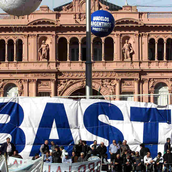 "Labor union leaders take part in a protest with a giant banner reading ""Basta"" (""Enough"") before the presidential palace in Buenos Aires in 2001. At the time, the country was mired in a three-year recession and facing default on its $128 billion public debt."