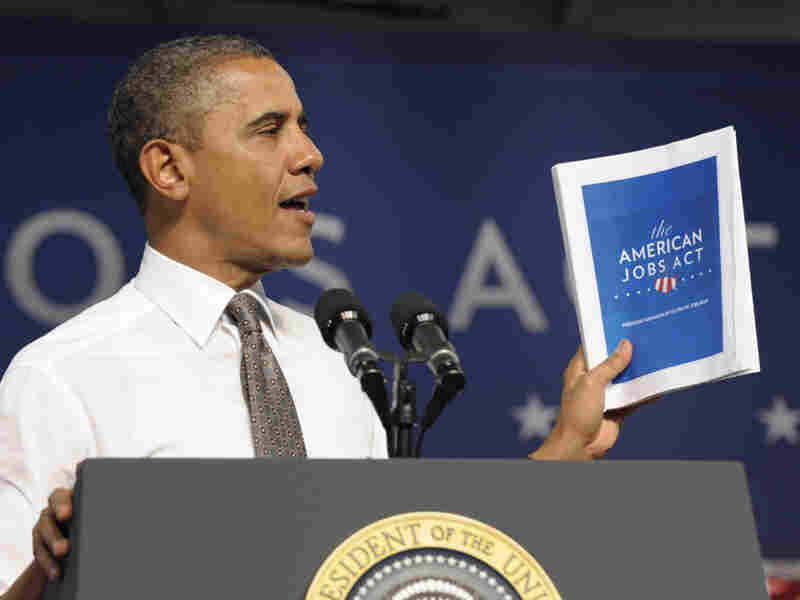 "President Obama holds up a copy of his jobs bill as he speaks at Eastfield College in Mesquite, Texas. Obama is challenging a divided Congress to unite behind the bill or get ready to be run ""out of town"" by angry voters."