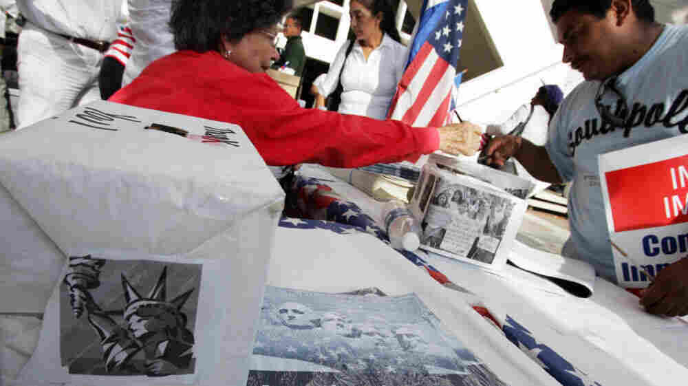 An immigrant signs a voter registration information card at a booth set up at a rally in downtown Miami in 2007. If a new law is upheld, the time period groups have to turn in new voter registrations will be reduced from 10 days to two.