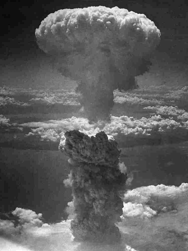 """A giant column of dark smoke rises more than 20,000 feet into the air after the second atomic bomb ever used in warfare exploded over Nagasaki, Japan, on Aug. 9, 1945. Dropped by the U.S. Army Air Force's B-29 plane """"Bockscar,"""" the bomb killed more than 70,000 people instantly, with tens of thousands dying later from effects of the radioactive fallout."""
