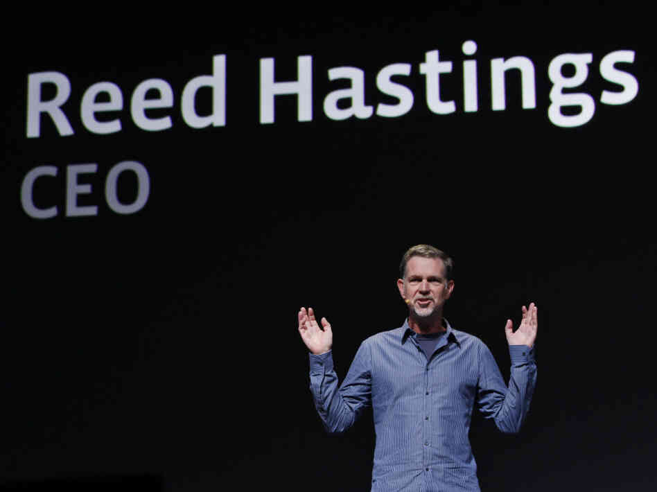 Netflix has backed off its unpopular plan to split its service into two offerings — one for streaming video, and one for sending DVDs by mail. CEO Reed Hastings is seen gesturing in this file photo.