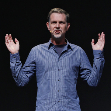 Netflix has backed off its unpopular plan to split its service into two offerings -- one for streaming video, and one for sending DVDs by mail. CEO Reed Hastings is seen gesturing in this file photo.