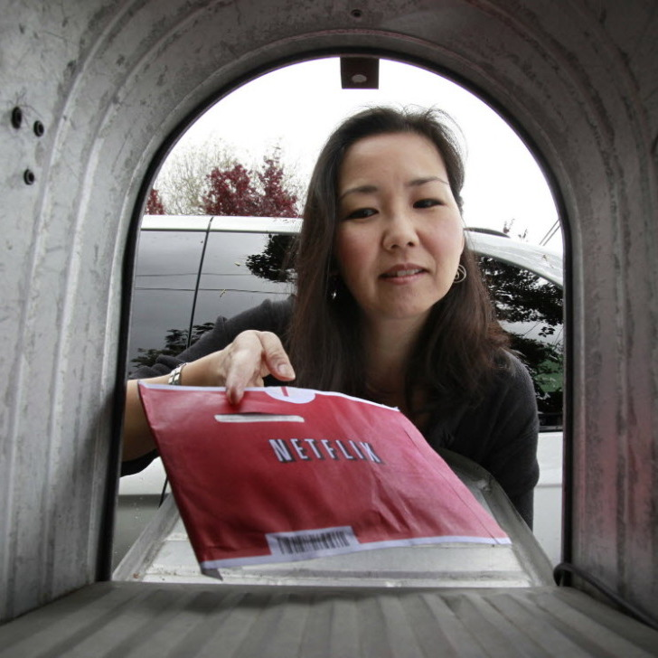 Carleen Ho picked up a Netflix movie from her mailbox in Palo Alto, Calif. The company announced Monday that it will not split its streaming and DVD video offerings.