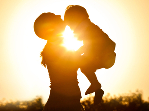 A mother holds her child at sunset.