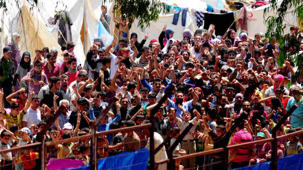 Syrian refugees gather to protest Syrian President Bashar Assad at the Turkish Red Crescent camp in the Yayladagi district of the Turkish city of Hatay near the Syrian border on June 20. More than 7,000 Syrians are living in camps in Turkey.