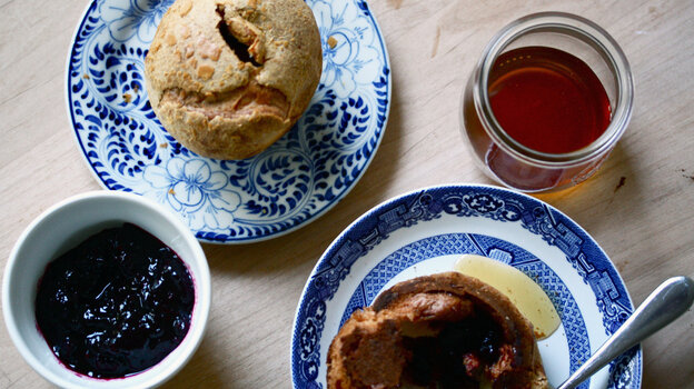 A table set with blackberry popover, blackberry jam and honey for serving