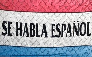 A sign spells out Se Habla Espanol (Spanish Spoken Here).