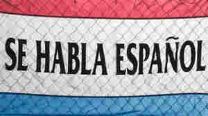 A sign spells out Se Habla Espanol (Spanish Spoken Here).