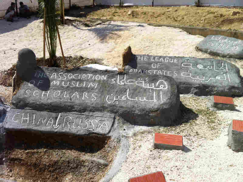 """At the Altinozu camp in southeastern Turkey, the Syrian residents have built a mock graveyard. A freshly dug """"grave"""" is for China and Russia, which vetoed a recent U.N. resolution against Syria. Other headstones are for the Arab League and the Association of Muslim Scholars, which have also disappointed the Syrian opposition."""