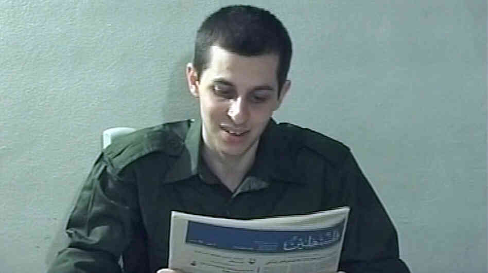 In this file image taken from a video released by Hamas in 2009, Israeli soldier Gilad Schalit is seen holding a newspaper in an unknown location.
