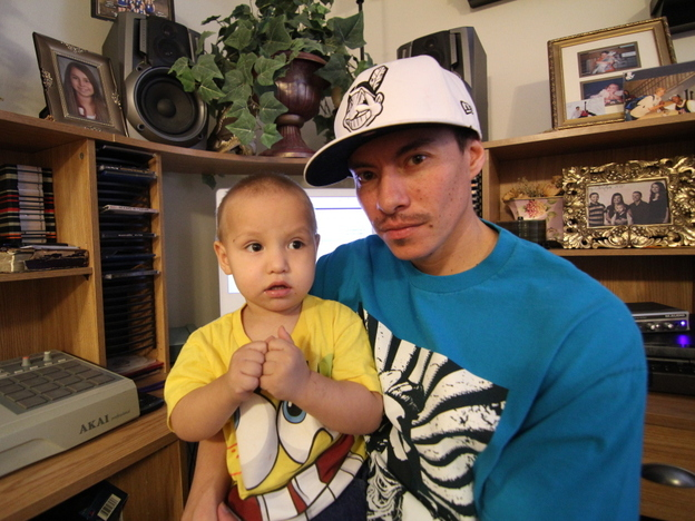 <p>Rapper Supaman with the great Crow Nation chief Plenty Coups on his shirt and his son, Brayden Lecrae, on his lap.</p>