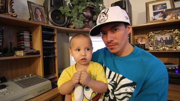 Rapper Supaman with the great Crow Nation chief Plenty Coups on his shirt and his son, Brayden Lecrae, on his lap.