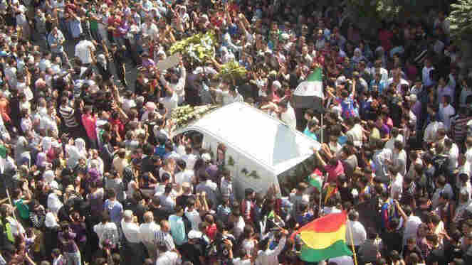 Mourners surround the hearse carrying the coffin of Kurdish opposition leader Meshaal al-Tammo during his funeral last Sunday in Amuda, in northern Syria. Supporters blamed the Syrian government for his death.