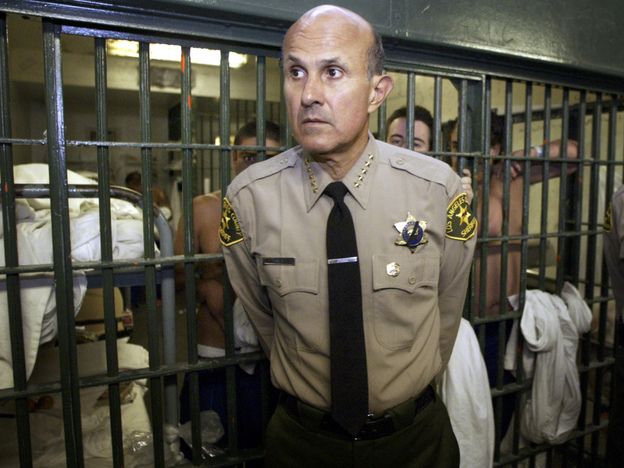 <p>Los Angeles County Sheriff Lee Baca leads a tour inside the men's central jail at the Twin Towers Correctional Facility in Los Angeles in 2004. Baca is accused of ignoring inmate abuse by his deputies. </p>