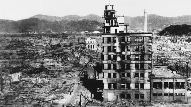 Survivors walk past one of the few building still standing in 1945,  two days after an atomic bomb was dropped on Hiroshima, Japan on August 6, 1945.