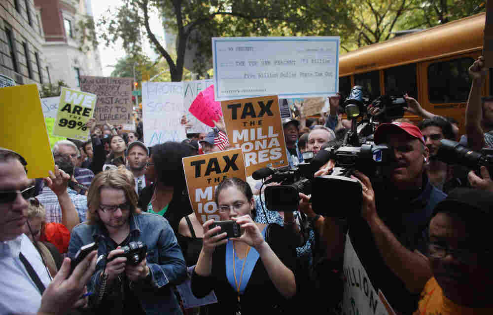 Protesters with Occupy Wall Street march along New York's 5th Avenue, where prominent heads of major business and financial institutions live, on Tuesday. The movement has expanded, along with media coverage.