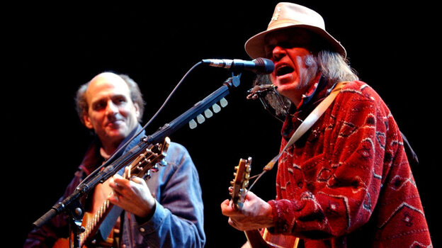 Neil Young performs with James Taylor at the 16th annual Bridge School benefit concert on Oct. 26, 2002.