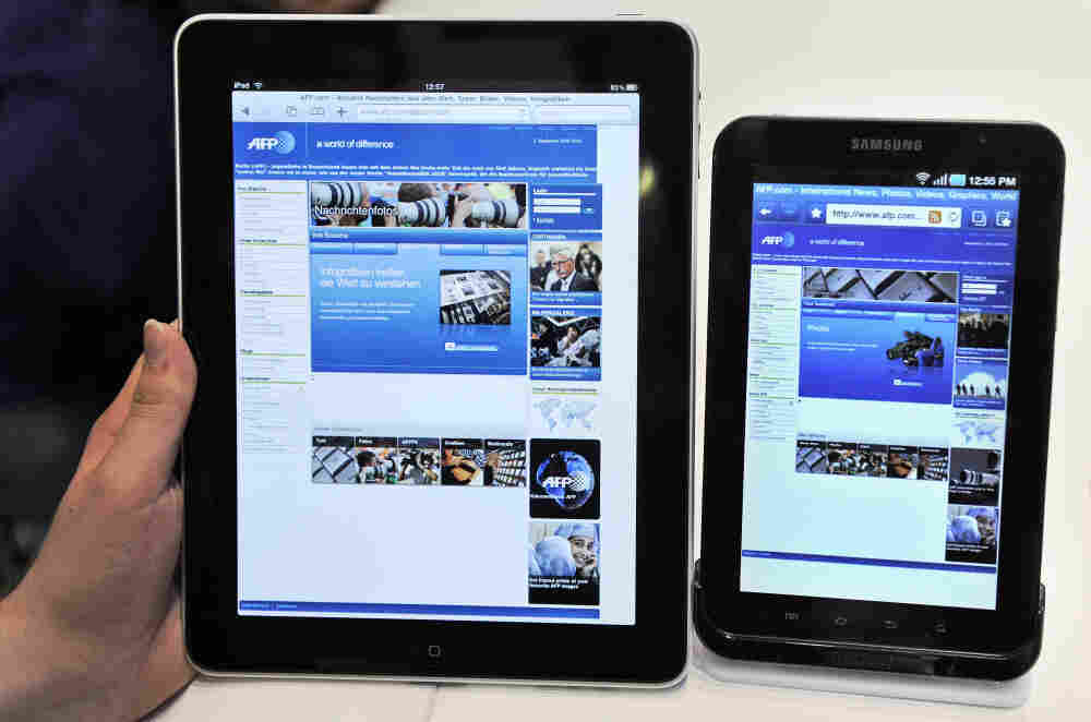 A woman holds an Apple iPad (L) next to a Samsung Galaxy Tab during the 50th International consumer electronics fair in Sept. 2010.