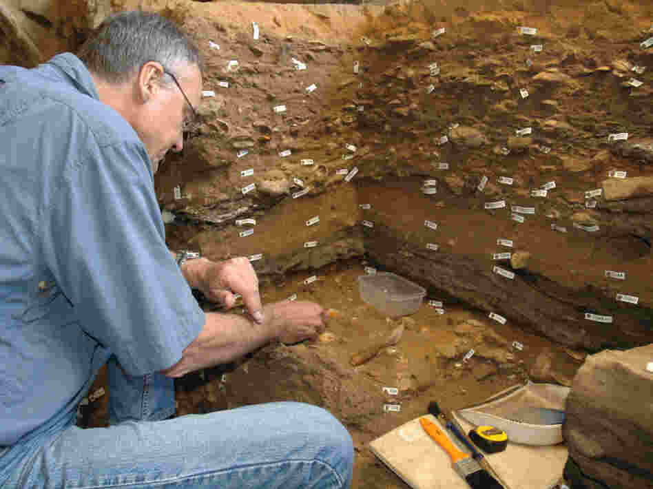Archaeologist Christopher Henshilwood excavates at the 100,000-year-old levels of the Blombos cave in South Africa.