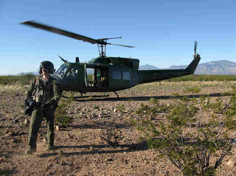 A member of a helicopter flight crew participating in Operation Angel Thunder walks across the desert in southern Arizona.