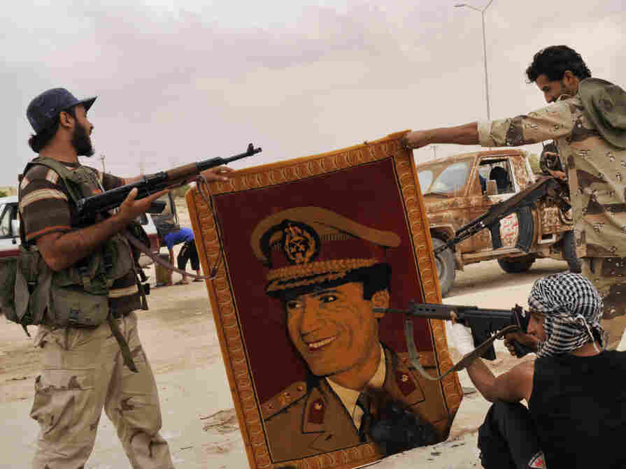 Anti-Gadhafi fighters point their guns at a carpet depicting Moammar Gadhafi after taking the village of Abu Hadi, the deposed Libyan leader's birthplace, on Oct. 3. Regime loyalists who fled to the village find themselves grappling with the realities of a new nation.