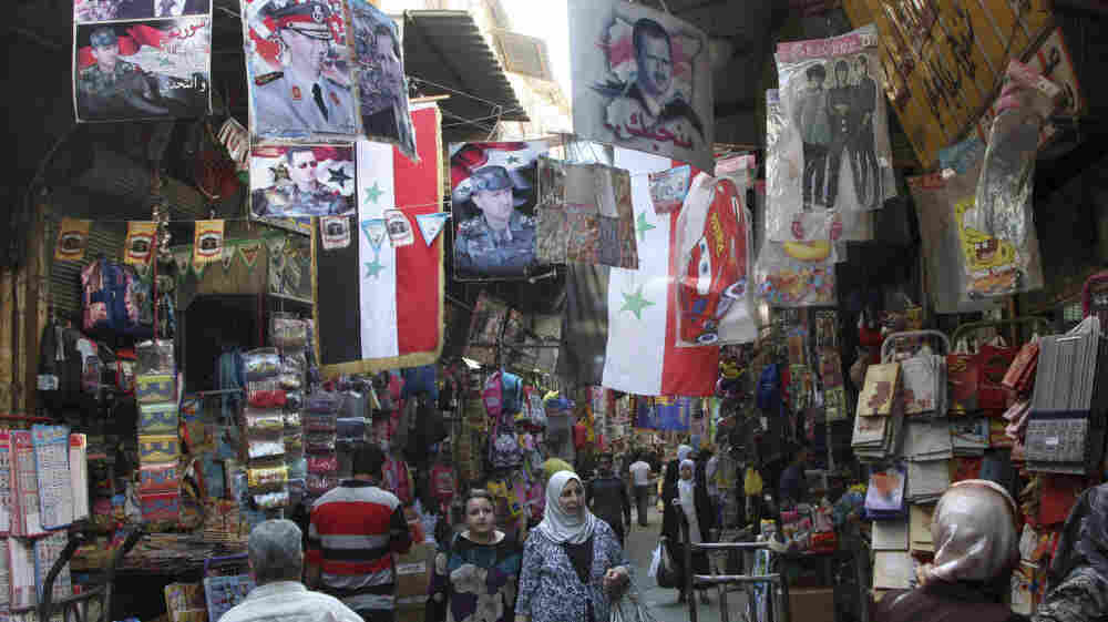 Syrians walk in the Hamidiyah market, decorated with portraits of President Bashar Assad and national flags, in the capital Damascus on Oct. 5. The European Union has intensified economic sanctions against Syria, but the crackdown against anti-regime protesters is unlikely to stop, Syrians say.