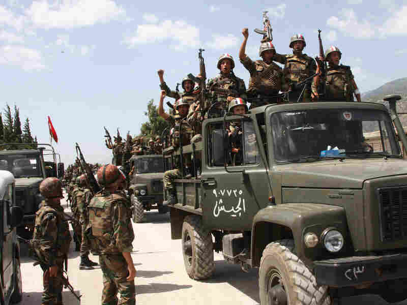In this photo taken during a government-organized visit for media, Syrian army soldiers shout slogans in support of Assad as they enter a village near the town of Jisr al-Shughour on June 10. Ongoing military operations to crush anti-government protest are draining money from the national budget.