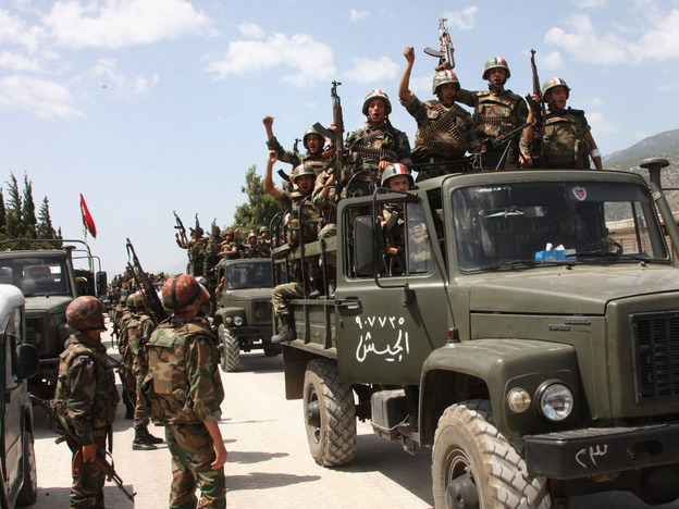 <p>In this photo taken during a government-organized visit for media, Syrian army soldiers shout slogans in support of Assad as they enter a village near the town of Jisr al-Shughour on June 10. Ongoing military operations to crush anti-government protest are draining money from the national budget.</p>
