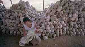 In this undated photo, a man cleans a skull near a mass grave at the Choeung Ek camp outside Phnom Penh, Cambodia — the best known of the killing fields run by the Khmer Rouge in the middle and late 1970s. Now, Cambodians are skeptical that a U.N.-backed tribunal will be able to deliver justice in the case of four remaining high-level Khmer Rouge officials.