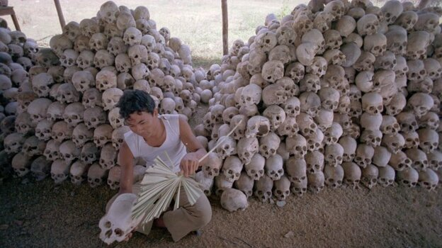 In this undated photo, a man cleans a skull near a mass grave at the Choeung Ek camp outside Phnom Penh, Cambodia — the best known of the killing fields run by the Khmer Rouge in the middle and late 1970s. Now, Cambodians are skeptical that a U.N.-backed tribunal will be able to deliver justice in the case of four remaining high-level Khmer Rouge officials. (AP)