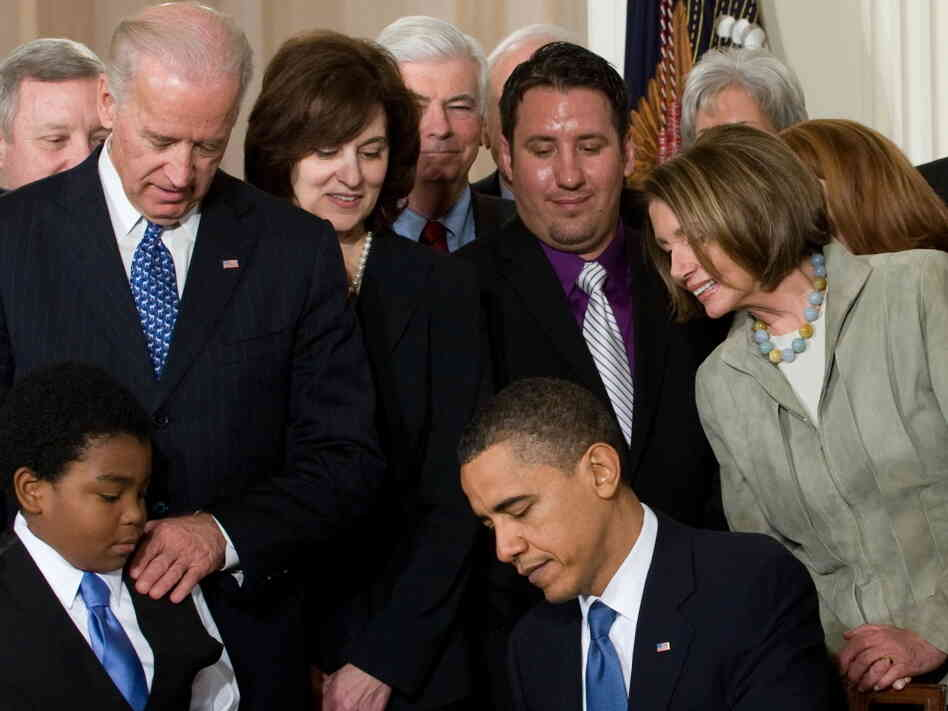 President Obama, surrounded by lawmakers and guests, signs health care insurance legislation during a ceremony in the East Room of the White House on March 23, 2010.