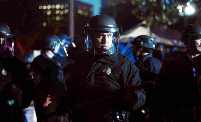 Dozens of police in riot gear pushed Occupy Denver protesters into retreat outside the state Capitol on Friday.