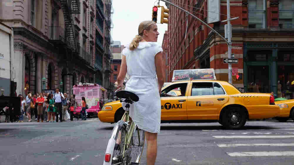 A woman rides down a Manhattan street on a bicycle in New York City. Like many major metropolitan areas, New York has witnessed a surge in bicycle use and plans to launch a bike-share plan by next summer.