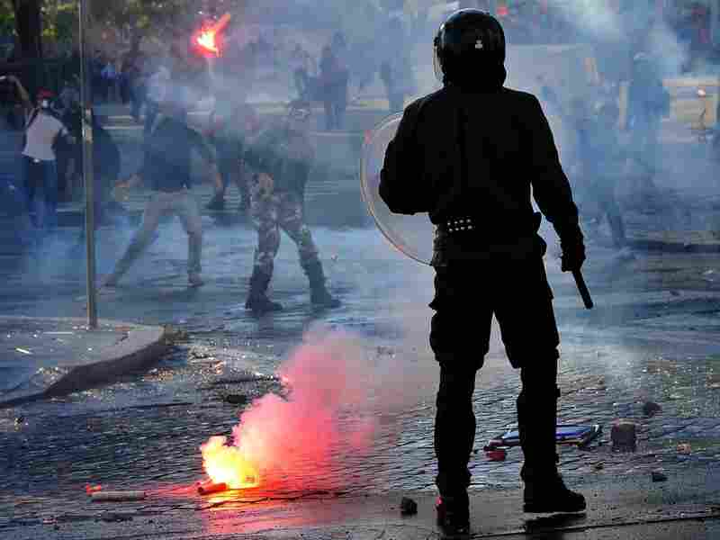 An anti-riot police officer stands as protesters launch flares in Rome after a demonstration turned into a riot Saturday.
