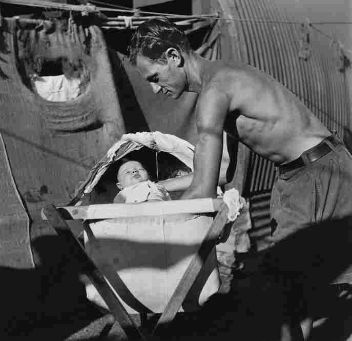 A father puts his baby to sleep in a bassinet constructed from gathered rags and pieces of wood, Cyprus Internment Camp, 1947