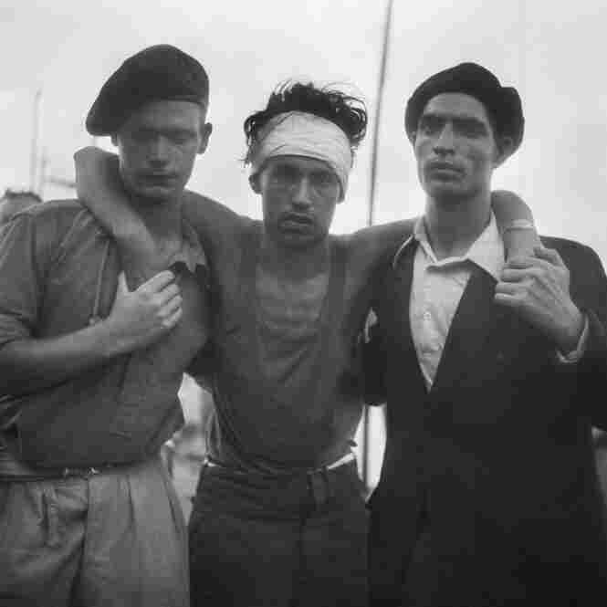 Wounded refugee aided by a British soldier and a friend, Haifa Port, July 18, 1947