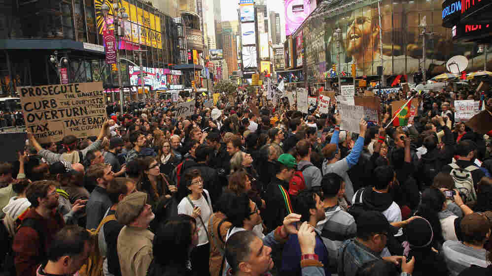 Demonstrators protest in New York's Time Square on Saturday. Thousands of people took to the streets in cities across the world, inspired by the Occupy Wall Street protests against economic inequality.
