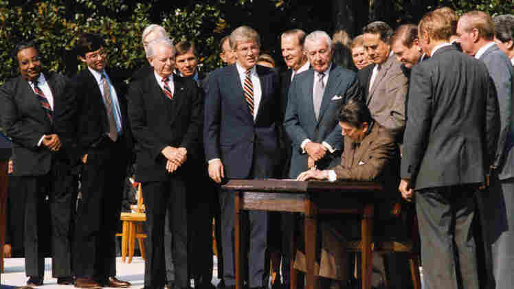 President Reagan signs the Tax Reform Act of 1986. The bipartisan reform shifted a large part of the tax burden from individuals to corporations and also exempted millions of low-income households from federal income taxes.