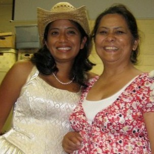 Malin Alegria often wears quinceanera dresses to her book readings. She says that when she was young, she had a hard time accepting the cultural pride her mother (right) tried to instill in her.