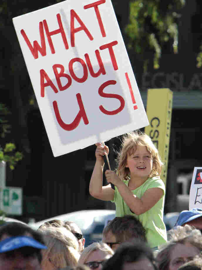 In California, where deep deficits have roiled the education system, a young protester holds a sign against layoffs and other cuts during a demonstration this past May.