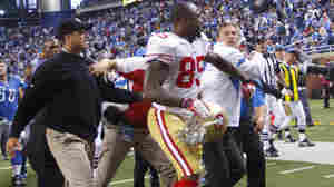 Harbaugh (in dark cap and jacket) and Schwartz (in white jacket with blue stripes) are separated by the 49ers' Venron Davis (85).