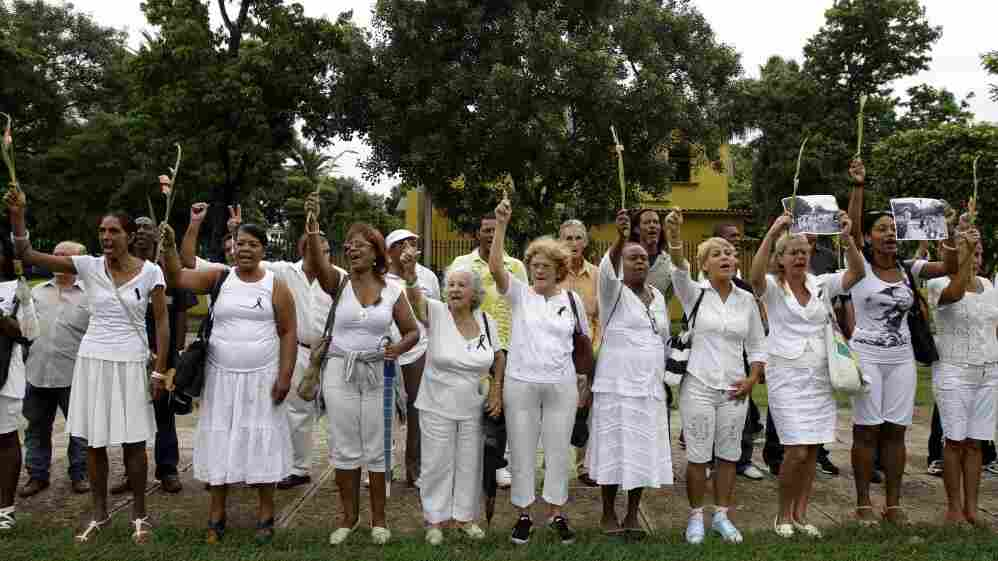 "Members of dissident group Ladies in White yell ""Laura lives!"" during their weekly march in front of Santa Rita church in Havana on Sunday. Cuba's Ladies in White have vowed to keep protesting against the island's Communist-run government despite the death of their late founder, Laura Pollan, but the loss presents new challenges for a dissident group already struggling to be visible."