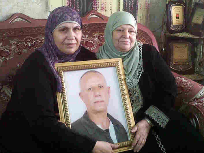 "Faizeh al-Maslamani (left) with her sister and a portrait of her husband, Ali, due to be released with more than 470 Palestinian prisoners Tuesday. Ali spent most of the past three decades in an Israeli jail. Faizeh says he has 10 grandchildren he's never seen. She hopes he'll accept ""a life sentence in the house."""