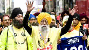 Fauja Singh, 100, celebrates at the finish line after completing the Toronto Waterfront Marathon in Toronto on Sunday, Oct. 16, 2011.