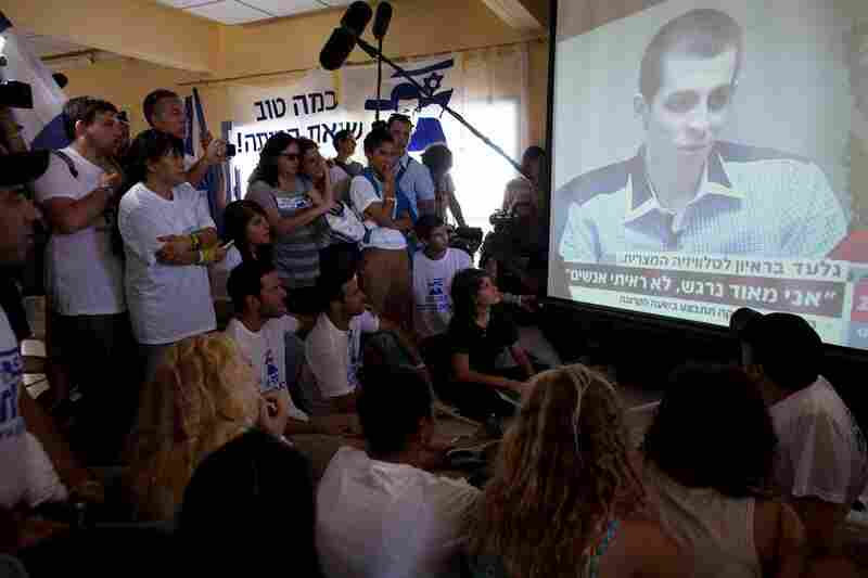 People in Mitzpe Hila watch the first televised images of the 25-year-old Shalit, who doctors said shows signs of malnutrition, following his release.