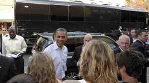 With his bus in the background, President Barack Obama greets people outside of Mast General Store in Boone, N.C., Monday. Obama is on a three-day bus tour promoting the American Jobs Act.