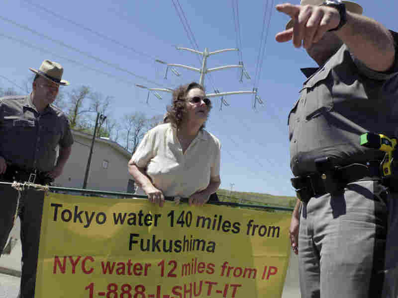 Marilyn Elie (center) of Cortlandt Manor, N.Y., is escorted off the grounds of the Indian Point Energy Center during a protest in May. Elie was there with a half-dozen others to voice opposition to the re-licensing of the nuclear facility.